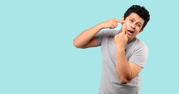 Uomo asiatico che tocca il suo fronte brufolo di spremitura, su fondo blu-chiaro in studio.