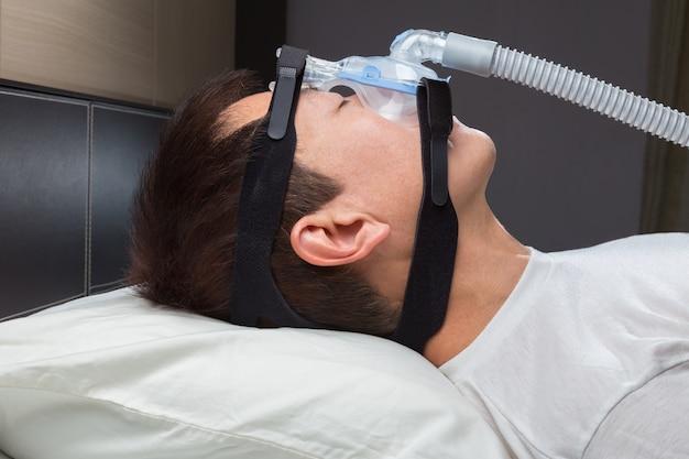 Uomo asiatico con apnea del sonno con macchina cpap