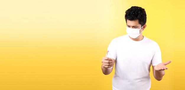 Uomo asiatico con gel per alcol e maschera medica, raccomandare la prevenzione di virus e varie malattie. isolato sulla parete gialla.
