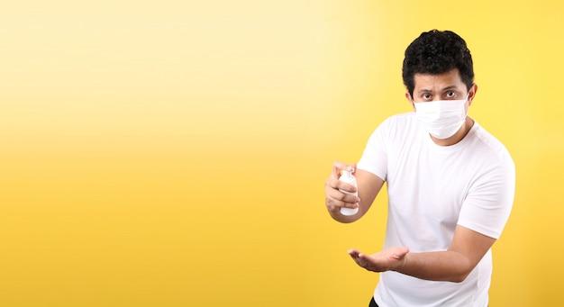 Uomo asiatico con gel per alcol e maschera medica, raccomandare la prevenzione di virus e varie malattie. isolato
