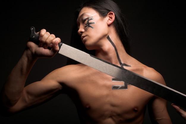 Uomo asiatico con katana sul nero