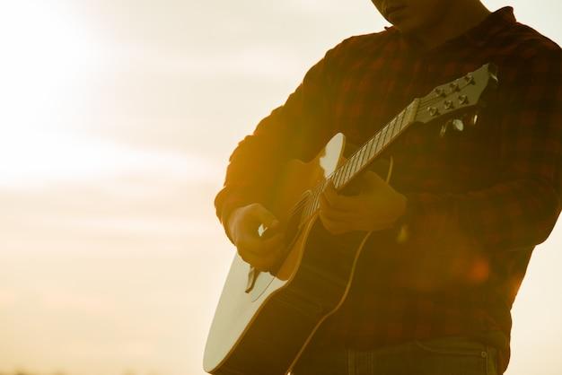 Uomo asiatico con la chitarra acustica durante il tramonto