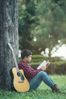 Uomo asiatico con la chitarra acustica in un parco