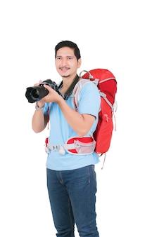 Uomo asiatico con uno zaino che tiene una macchina fotografica per scattare foto