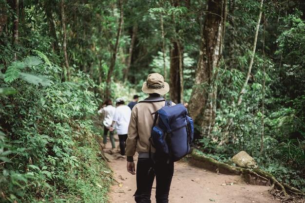 Uomo asiatico con zaino e cappello in montagna
