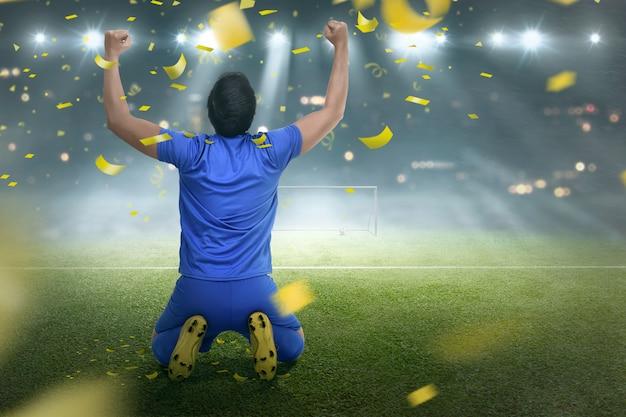 Uomo asiatico del giocatore di calcio di felicità dopo la conquista della partita