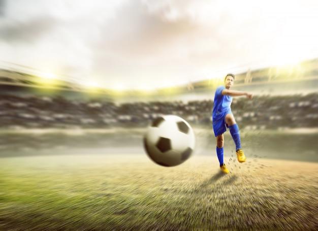 Uomo asiatico del giocatore di football americano che dà dei calci alla palla
