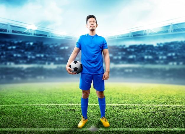 Uomo asiatico del giocatore di football americano che tiene la palla nel mezzo