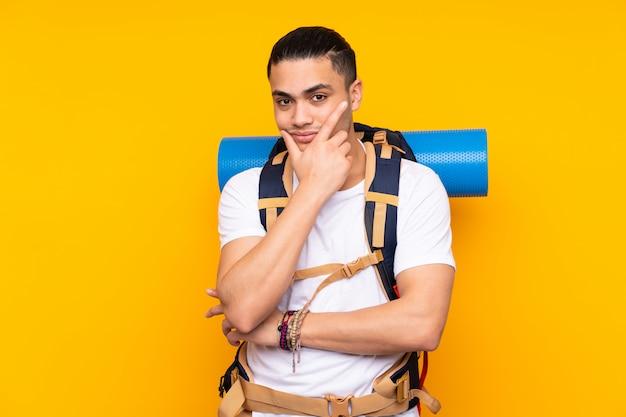 Uomo asiatico del giovane alpinista con un grande zaino sulla parete gialla che pensa un'idea