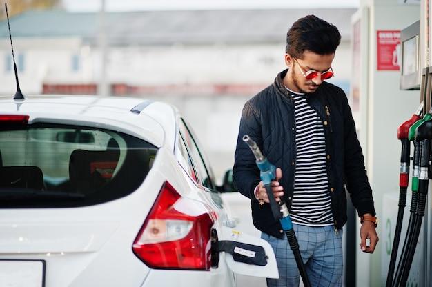 Uomo asiatico del sud o maschio indiano che rifornisce di carburante la sua automobile bianca sulla stazione di servizio.