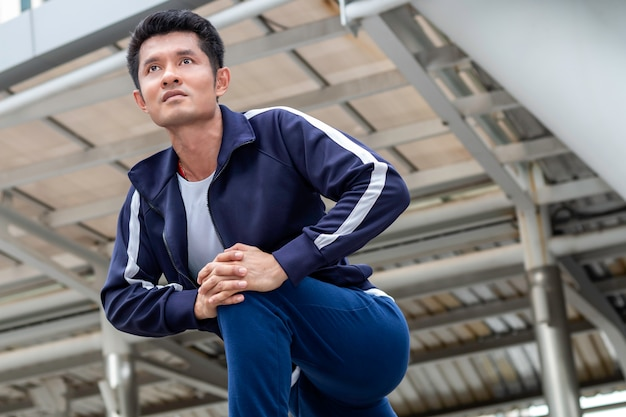 Uomo asiatico dell'atleta nella posa di inizio corrente sulla via della città.