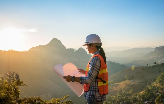 Uomo asiatico dell'ingegnere che esamina il modello con il tramonto sull'intervallo di montagne
