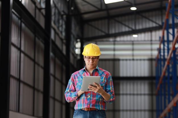 Uomo asiatico dell'ingegnere che lavora nella fabbrica della costruzione