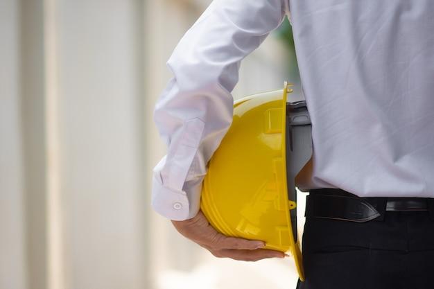 Uomo asiatico di affari che tiene cappello duro sulla costruzione del sito