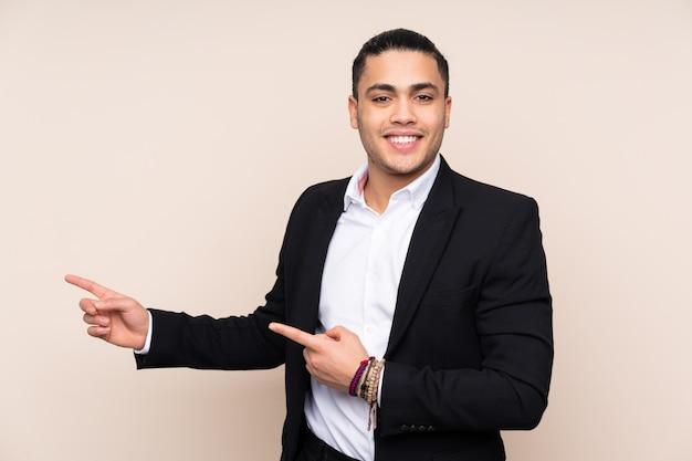 Uomo asiatico di affari sulla parete beige che indica dito il lato