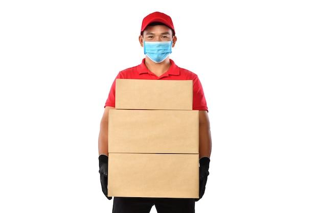 Uomo asiatico di consegna che indossa la maschera e guanti in uniforme rossa che consegna la cassetta dei pacchi isolata su bianco durante lo scoppio di covid-19