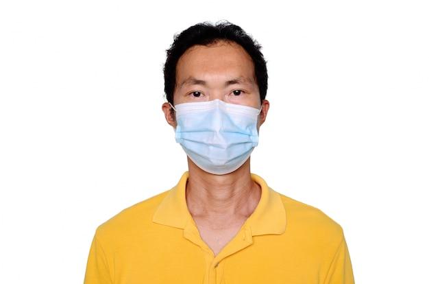Uomo asiatico di mezza età in maglietta blu che indossa mascherina medica, isolata su priorità bassa bianca. coronavirus o concetto di protezione covid-19.
