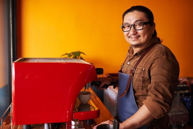 Uomo asiatico di mezza età sorridente in grembiule che sta accanto alla macchina e al sorridere del caffè espresso