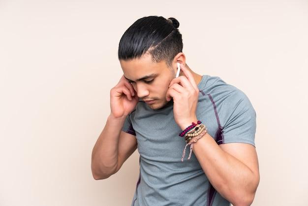 Uomo asiatico di sport su musica d'ascolto della parete beige