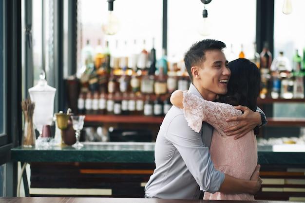 Uomo asiatico e donna che abbracciano nella barra