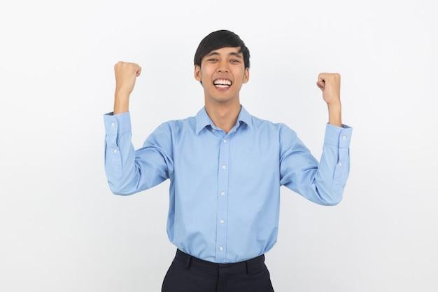 Uomo asiatico emozionante di giovani affari che alza i pugni con il fronte felice felice, celebrante successo