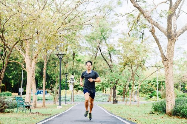 Uomo asiatico felice che funziona nel parco in mattina