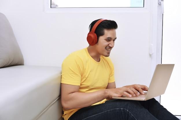 Uomo asiatico felice che si siede con il computer portatile e le cuffie