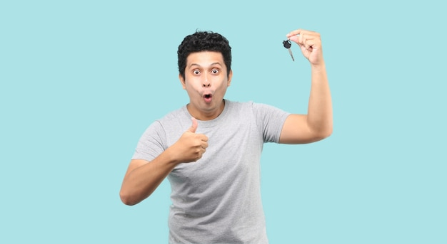 Uomo asiatico felice che tiene una chiave dell'automobile e che dà pollice in su