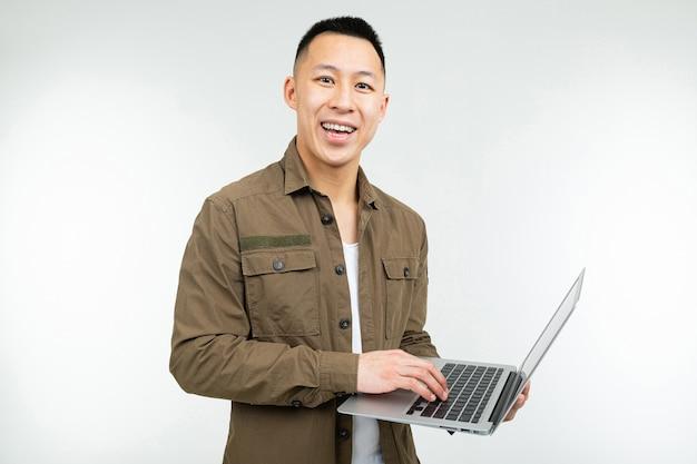 Uomo asiatico felice sorridente che tiene un computer portatile in sue mani su un fondo bianco dello studio