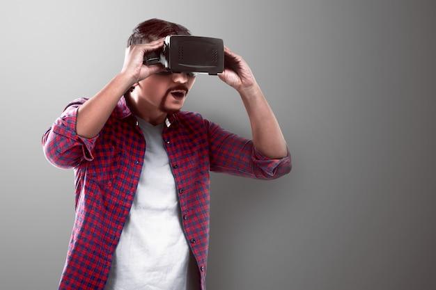 Uomo asiatico guardando qualcosa sulla cuffia di realtà virtuale