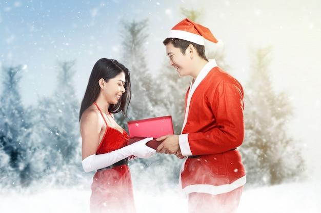 Uomo asiatico in costume di santa che dà alla sua ragazza un contenitore di regalo