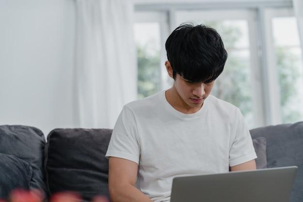 Uomo asiatico indipendente che lavora a casa, maschio creativo sul computer portatile sul sofà in salone. imprenditore proprietario giovane uomo d'affari, giocare a computer, controllando i social media sul posto di lavoro a casa moderna.