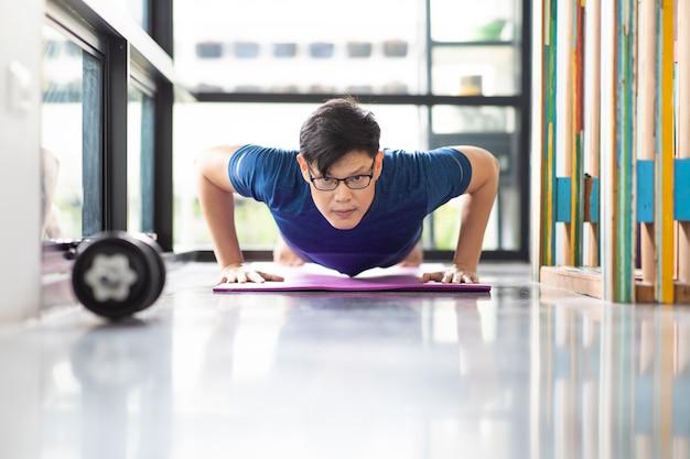 Uomo asiatico maturo che fa gli esercizi a casa. allenamento a casa. riduzione dei contatti.