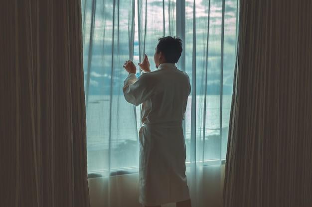 Uomo asiatico nell'apertura del vestito dell'accappatoio e facente un giro turistico la spiaggia del mare quando svegliarsi