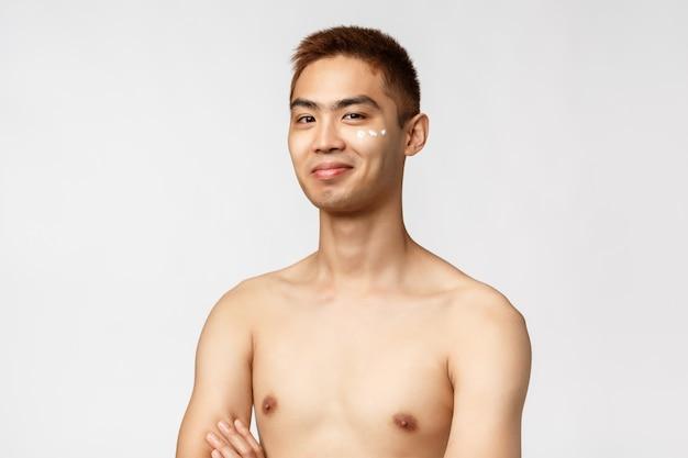 Uomo asiatico nudo del ritratto che mostra gesto.