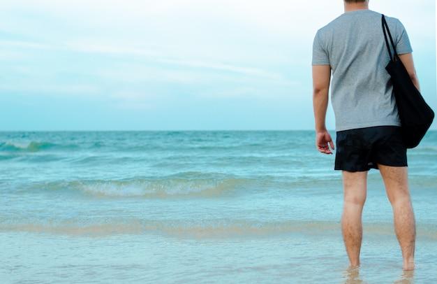 Uomo asiatico rilassante sulla spiaggia.