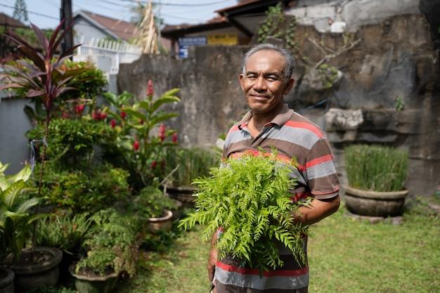 Uomo asiatico senior con alcune piante sulla sua mano