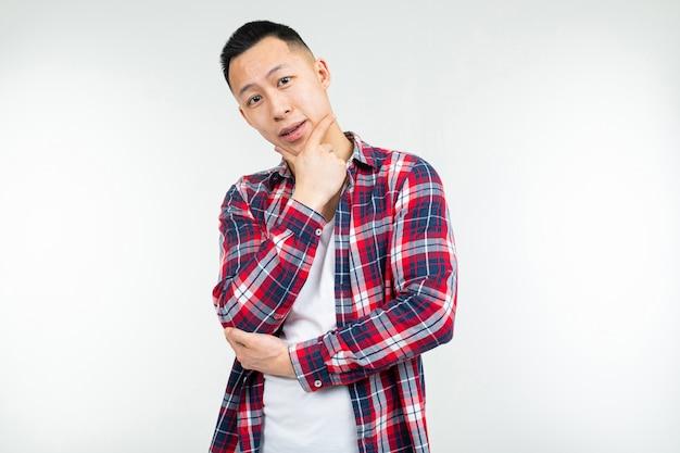 Uomo asiatico sicuro in una camicia di plaid spalancata su un fondo bianco dello studio con lo spazio della copia