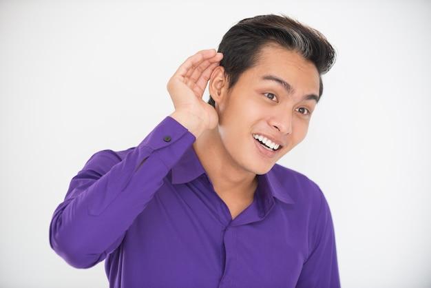 Uomo asiatico sorridente che cupa mano dietro l'orecchio