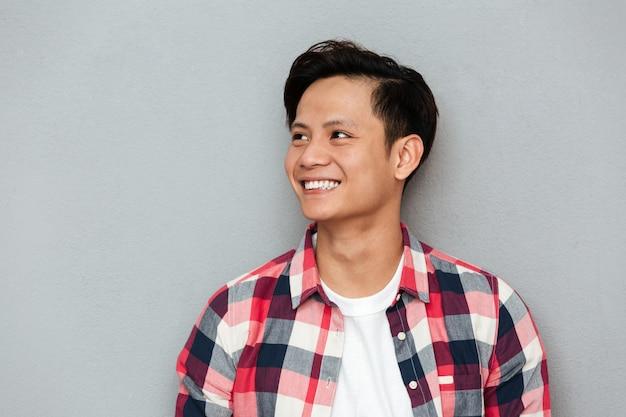 Uomo asiatico sorridente dei giovani che controlla parete grigia.