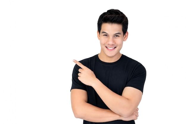 Uomo asiatico sorridente felice che indica mano per svuotare spazio da parte