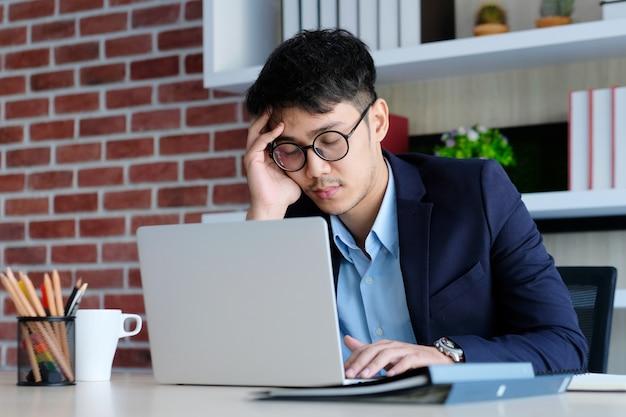 Uomo asiatico stanco che dorme alla scrivania