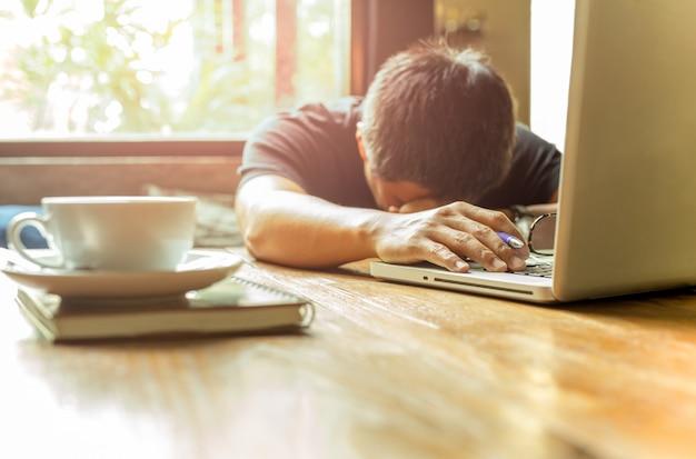Uomo asiatico stanco con la testa giù sul computer portatile del computer mentre lavorando.