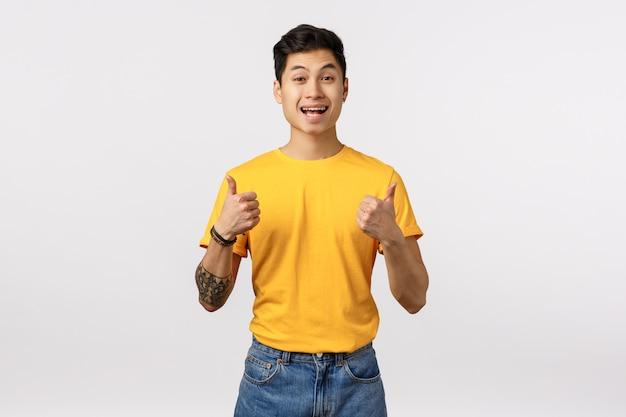 Uomo asiatico sveglio in maglietta gialla che dà i pollici in su