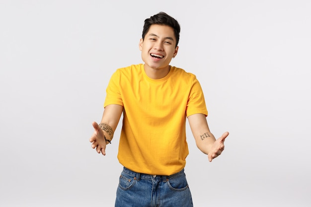 Uomo asiatico sveglio in maglietta gialla che dà un abbraccio