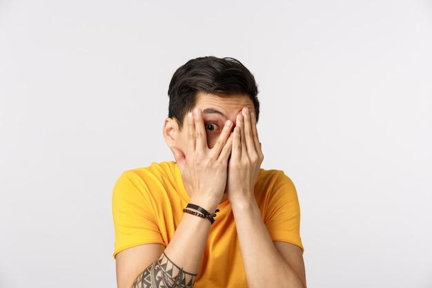 Uomo asiatico sveglio in maglietta gialla che dà una occhiata tramite le dita