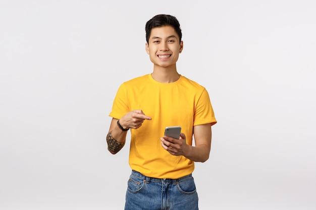 Uomo asiatico sveglio in maglietta gialla facendo uso dell'app impressionante