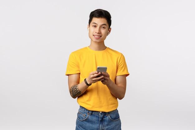 Uomo asiatico sveglio in maglietta gialla facendo uso dello smartphone