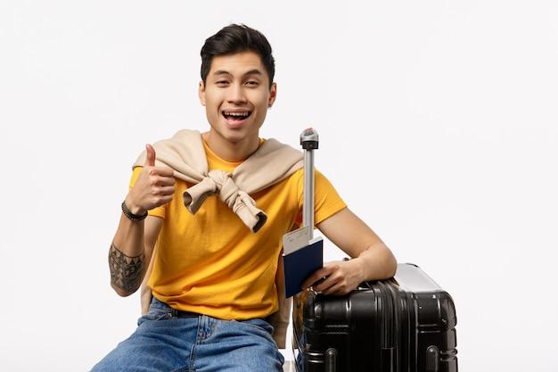 Uomo asiatico sveglio in maglietta gialla pronta a viaggiare con la borsa del carrello e del passaporto