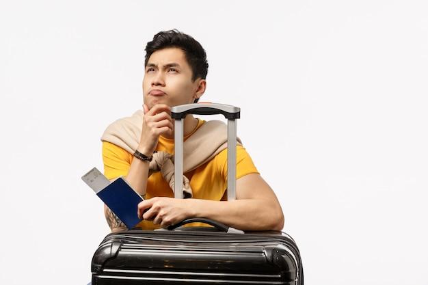 Uomo asiatico sveglio in maglietta gialla pronta per un viaggio che tiene un passaporto